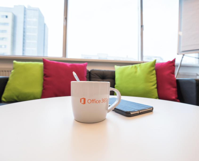 Auf diesem Foto sind die Couch des Büros und der Couchtisch abgebildet. Auf dem Tisch steht ein Becher Kaffee. Ein Microsoft Device liegt daneben.