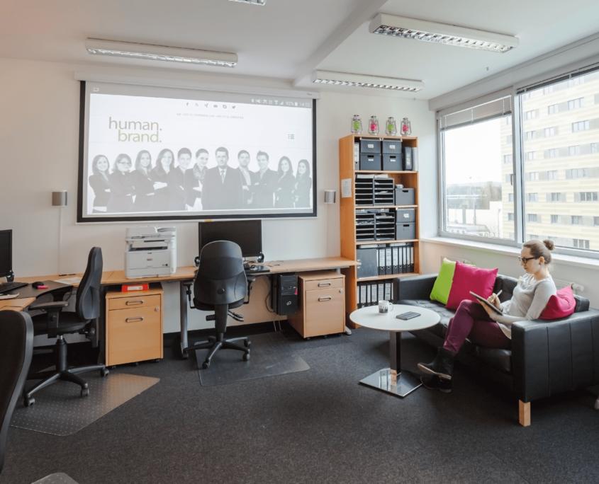 Auf diesem Foto ist der kleinere Raum mit Couch und Beamer-Leinwand abgebildet. Eine Mitarbeiterin von Humanbrand sitzt auf der Couch und arbeitet auf ihrem Surface.