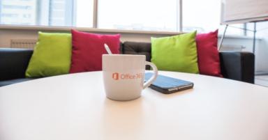 Es ist ein Kaffeetisch, auf dem eine Office 365 Tasse und ein Telefon abgebildet. Im Hintergrund ein Sofa mit grünen und rosa Kissen.