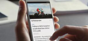 Auf dem Bildschirm eines Handys wird ein Zeitungsartikel über Radfahren angezeigt. Das Handy wird mit einer Hand gehalten, die andere tippt mit einem Finger auf den Bildschirm.