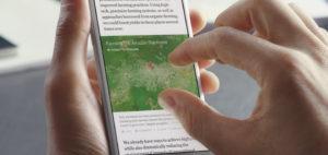 Auf dem Bildschirm eines Handys wird ein Zeitungsartikel über Landwirtschaft angezeigt. Das Handy wird mit einer Hand gehalten, die andere tippt mit zwei Fingern auf den Bildschirm, um das Bild zu vergrößern.