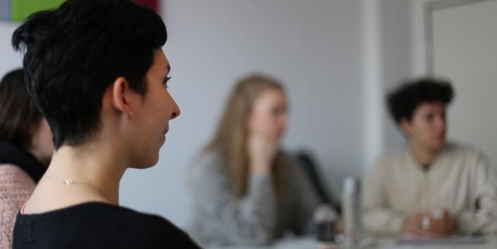 Auf dem Bild erkennt man Julia seitlich bei einem Ads-Meeting mit mehren Kollegen im Hintergrund.