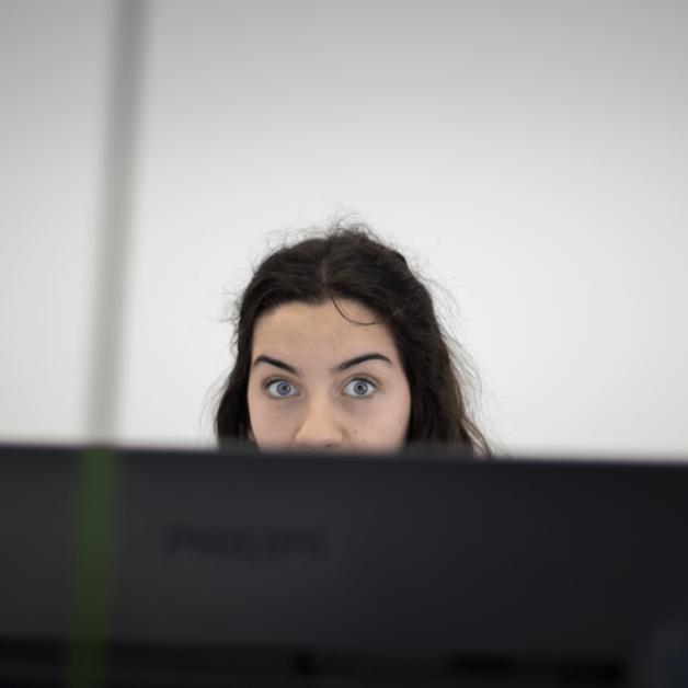 Das Bild zeigt eine Mitarbeiterin der Redaktionsabteilung. Die untere Hälfte ihres Gesichts ist von einem Bildschirm verdeckt.