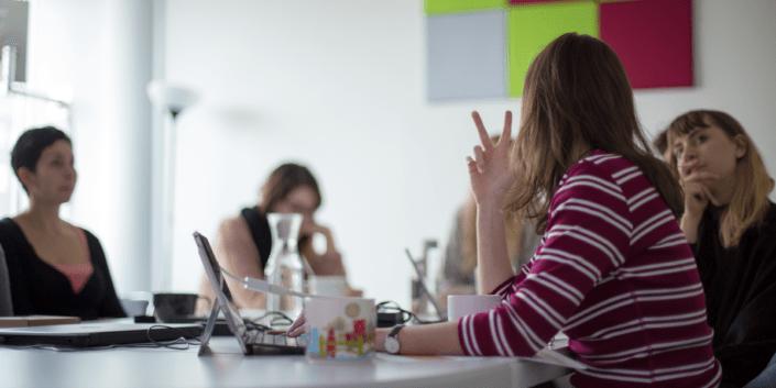 Auf dem Bild sieht man ein Ads-Meeting mit einigen Frauen im Besprechungsraum.
