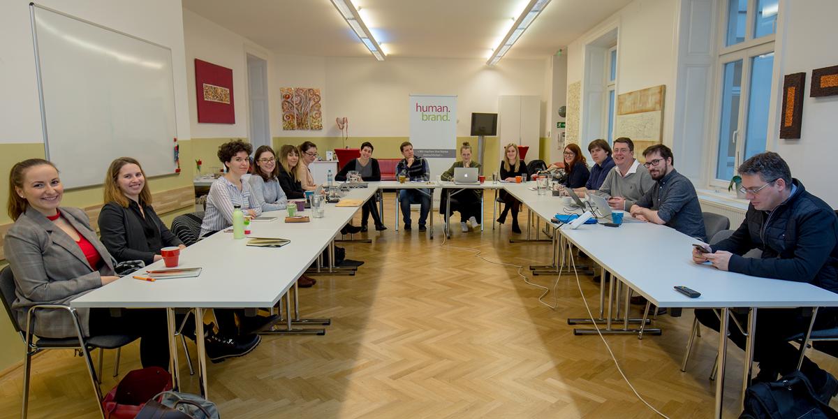 Die HUMANBRAND-Mitarbeiter nehmen im Veranstaltungsraum der HUMANBRAND Media Academy an einer internen Fortbildung teil.