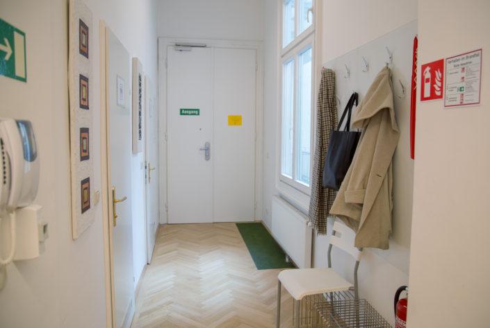 Das Foto zeigt den Eingangsbereich beziehungsweise Flur der HUMANBRAND Media Academy. Er ist mehrheitlich in weiß gehalten und hat einen hellen Holzboden. Auf der rechten Seite befindet sich eine Garderobe, auf der eine Jacke, Tasche und ein Schal hängen.