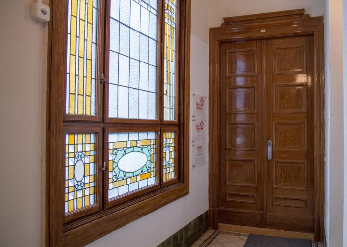 Das Bild zeigt die Eingangstüre der HUMANBRAND Media Academy sowie einen kleinen Ausschnitt des Hausflurs. Auf der linken Seite ist ein buntes Glasfenster zu sehen.