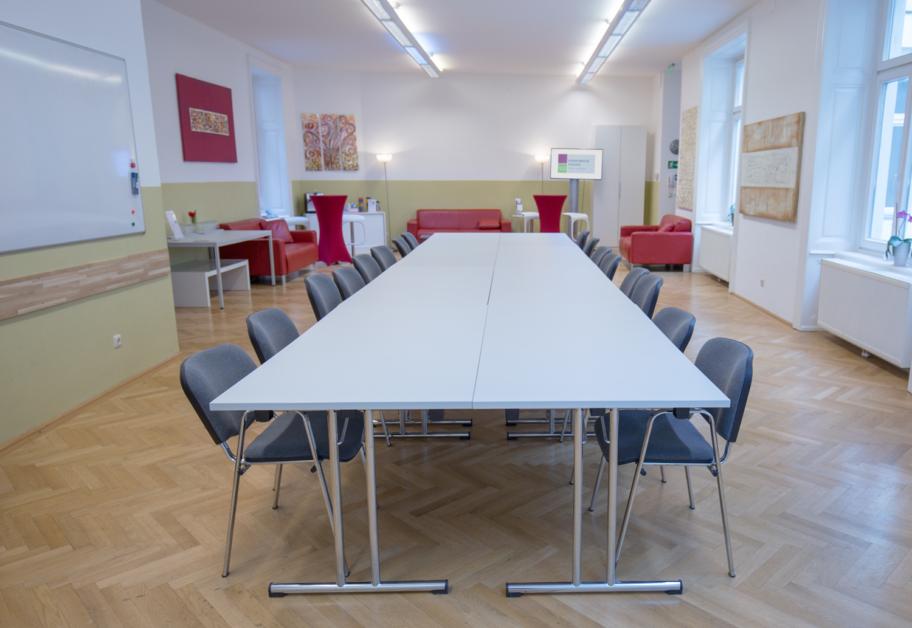 Ein Foto des Veranstaltungsraumes der HUMANBRAND Media Academy mit I-Bestuhlung. Dabei stehen immer zwei Tische gegenüber voneinander, sodass am Tisch sitzende Personen einander gegenübersitzen würden. Im Hintergrund befindet sich der Pausenbereich.