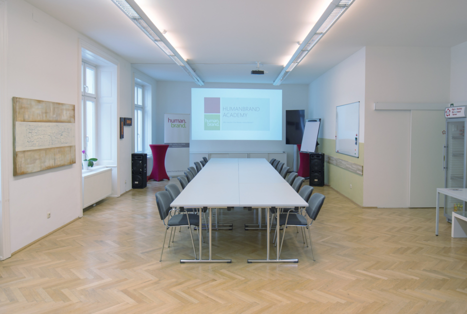 Ein Foto des Veranstaltungsraumes der HUMANBRAND Media Academy mit I-Bestuhlung. Dabei stehen immer zwei Tische gegenüber voneinander, sodass am Tisch sitzende Personen einander gegenübersitzen würden. Im Hintergrund befindet sich der Präsentationsbereich mit Leinwand.