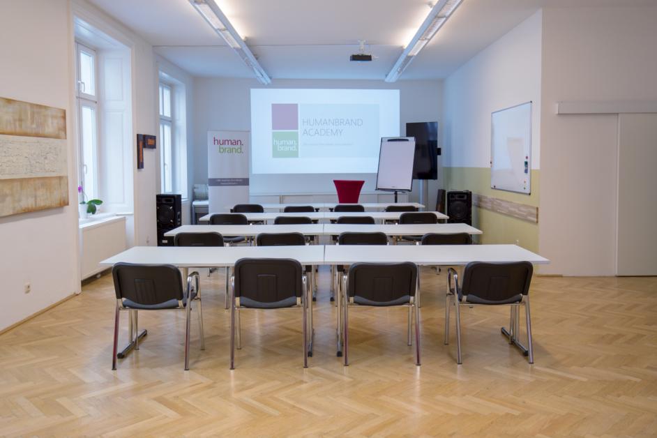 Zu sehen ist der Veranstaltungsraum der HUMANBRAND Media Academy mit einer Bestuhlung in Form einer Schulkasse. In 4 Reihen sind jeweils 2 Tische mit 4 Sesseln in Richtung Leinwand platziert.