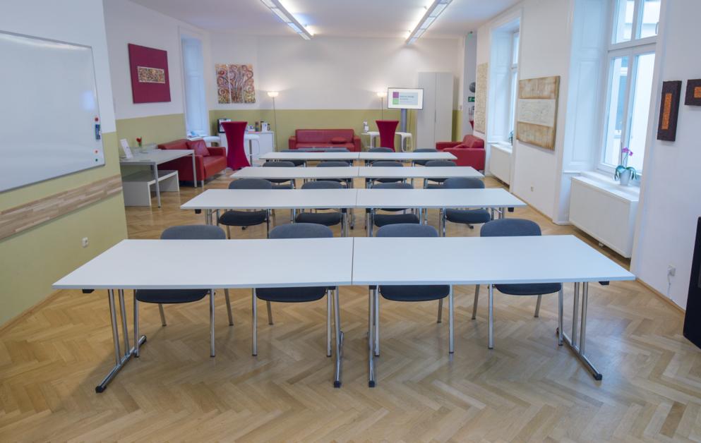 Zu sehen ist der Veranstaltungsraum der HUMANBRAND Media Academy mit einer Bestuhlung in Form einer Schulkasse aus Sicht einer vorne im Präsentationsbereich stehenden Person. In 4 Reihen sind jeweils 2 Tische mit 4 Sesseln in Richtung Leinwand platziert. Im Hintergrund ist der Pausenbereich zu sehen.