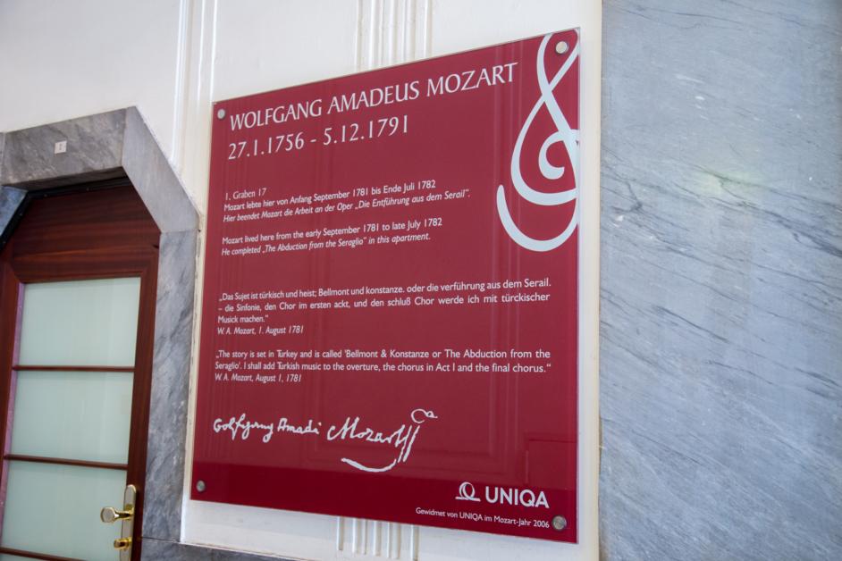 Auf dem Bild sieht man ein rotes Schild an der Hauswand, welches erklärt, dass Wolfgang Amadeus Mozart eine Zeit lang im Haus gewohnt hat, in dem sich die HUMANBRAND Media Academy befindet.