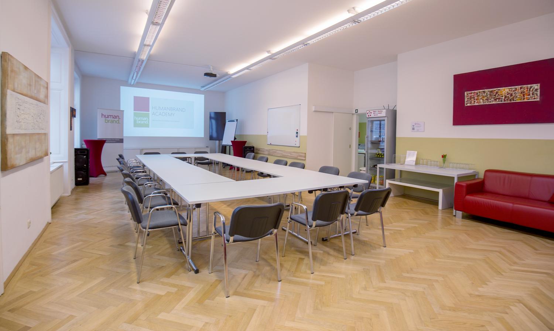 Ein Foto des Veranstaltungsraumes der HUMANBRAND Media Academy mit O-Bestuhlung. Dabei stehen die Tische so, dass sie einen geschlossenen Kreis ergeben. Im Hintergrund befindet sich der Präsentationsbereich mit Leinwand.