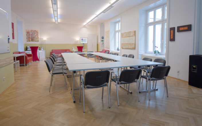 Ein Foto des Veranstaltungsraumes der HUMANBRAND Media Academy mit O-Bestuhlung. Dabei stehen die Tische so, dass sie einen geschlossenen Kreis ergeben. Im Hintergrund befindet sich der Pausenbereich.