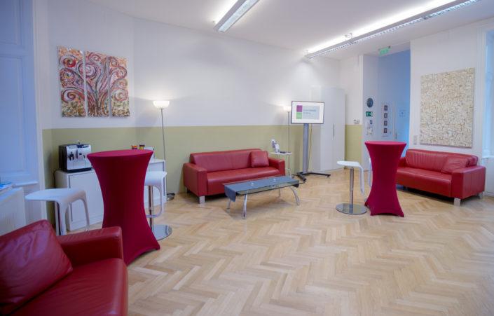 Ein Bild des Pausenbereiches der HUMANBRAND Media Academy. Abgebildet sind drei rote Ledersofas sowie zwei Stehtische inklusive Barhockern.