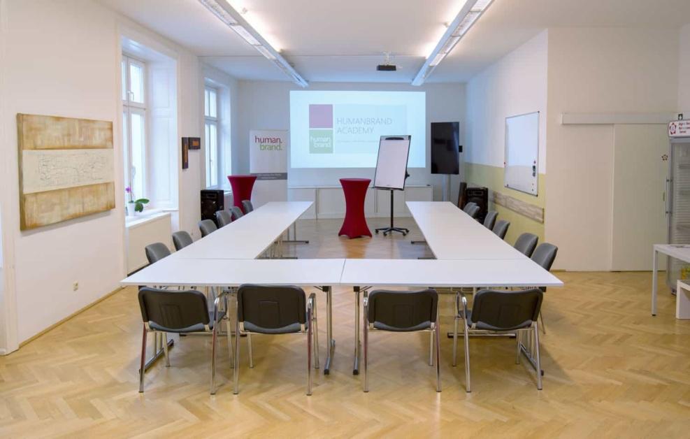 Ein Foto des Veranstaltungsraumes der HUMANBRAND Media Academy mit U-Bestuhlung, welche nach vorne hin zum Präsentationsbereich mit der Leinwand geöffnet ist.