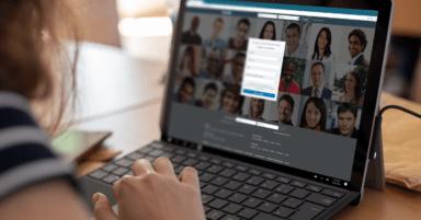 Eine Frau arbeitet an einem Surface Pro, auf dessen Bildschirm die Startseite von LinkedIn zu sehen ist.