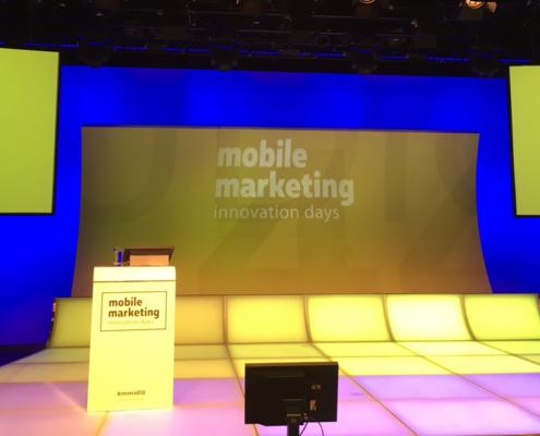 Zu sehen ist die Bühne der Mobile Marketing Innovation Days. Der Boden besteht aus leuchtenden Fliesen, welche im Vordergrund violett, im Hintergrund gelb leuchten. Links auf der Bühne steht ein Rednerpult mit eingebautem Bildschirm. Im Hintergrund ist eine gelbe Plakatwand zu sehen, auf der der Name der Veranstaltung steht.