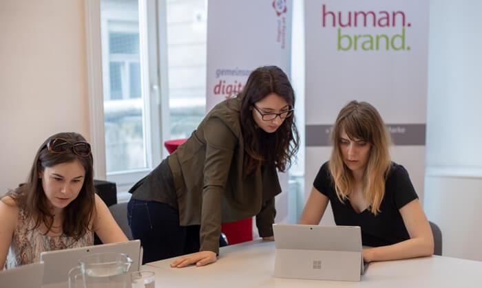 Zwei Frauen sitzen an einem Tisch und arbeiten jeweils auf ihrem Laptop. Zwischen den beiden steht eine weitere Frau, sie lehnt sich an den Tisch und sieht der Frau rechts im Bild über die Schulter ebenso auf den Laptop.