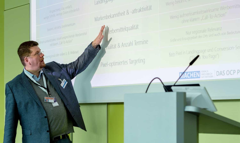 HUMANBRAND-Geschäftsführer Christian Haberl hält einen Vortrag und zeigt dabei auf eine Leinwand, auf der eine Präsentation zum Thema Paid Social Media zu sehen ist.