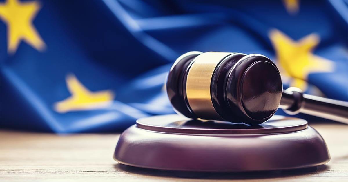 Das Bild zeigt einen Richterhammer vor der europäischen Flagge.