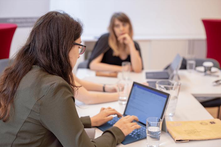 Drei Personen sind bei einem Meeting in der HUMANBRAND Media Academy zu sehen.