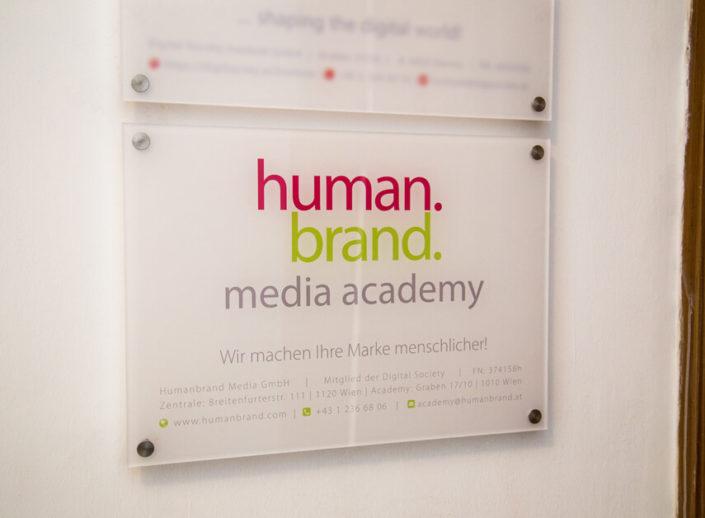 """Das Bild zeigt das Türschild der HUMANBRAND Media Academy. Auf dem Schild befindet sich das Logo sowie der Slogan """"Wir machen Ihre Marke menschlicher!"""" Außerdem werden die Kontaktdaten aufgelistet, welche sich auch am unteren Ende der Webseite befinden."""