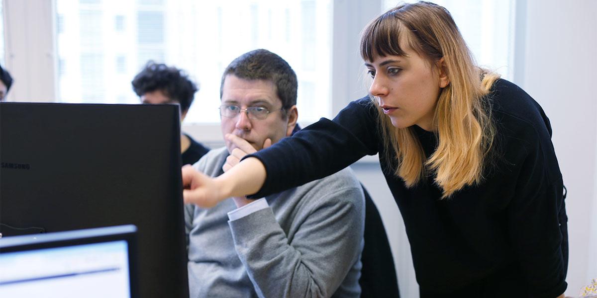 Katharina zeigt Christian etwas auf einem Bildschirm. Dabei zeigt sie mit einer Hand auf den Bildschirm, während Christian gespannt zusieht.
