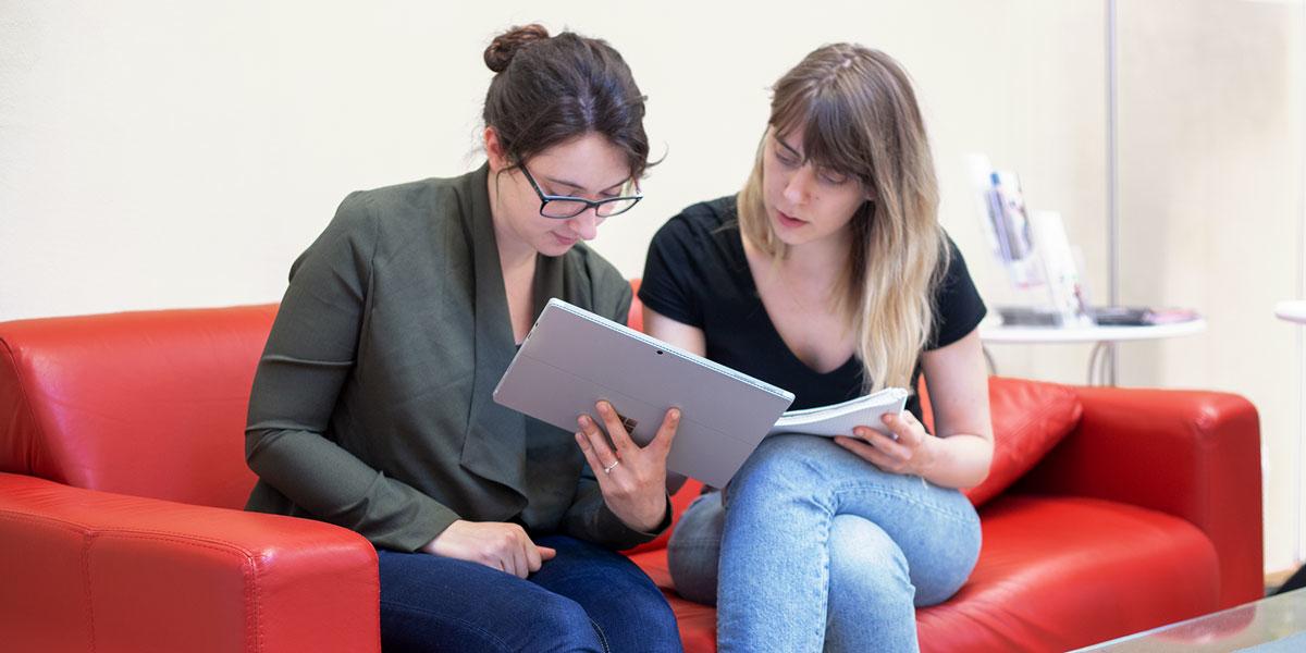 Petra und Katharina sitzen auf einem roten Sofa und schauen auf ein Surface Tablet, das Petra in der Hand hält.