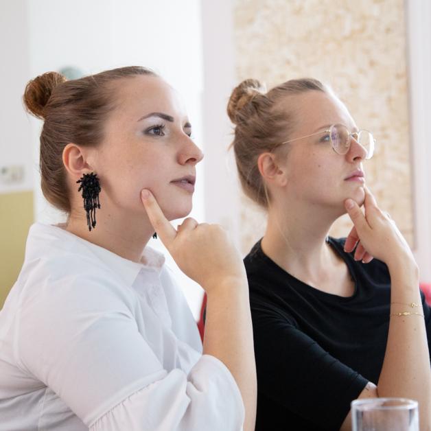 Zwei Mitarbeiterinnen lauschen interessiert einem Workshop in der HUMANBRAND Media Academy.
