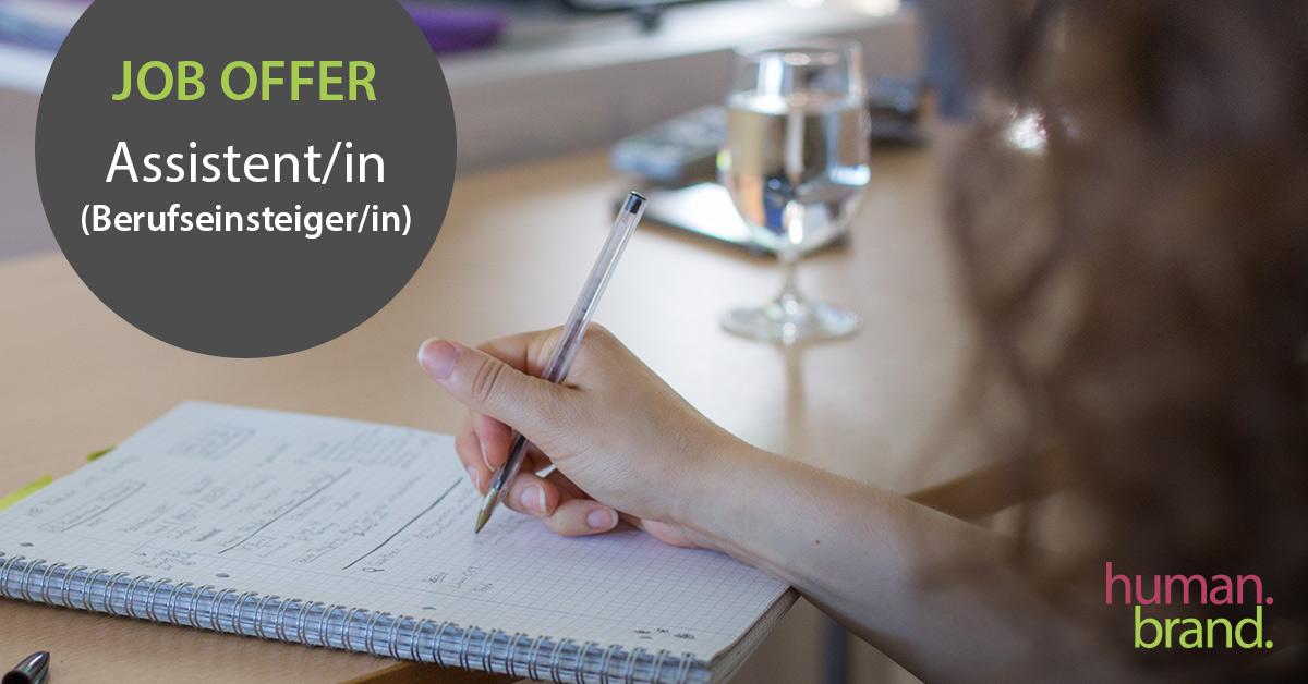 """Eine Frau macht auf einem Collegeblock Notizen. Links im Bild ist ein graues Feld mit dem Text """"Job Offer Assistent/in (Berufseinsteiger/in)""""."""