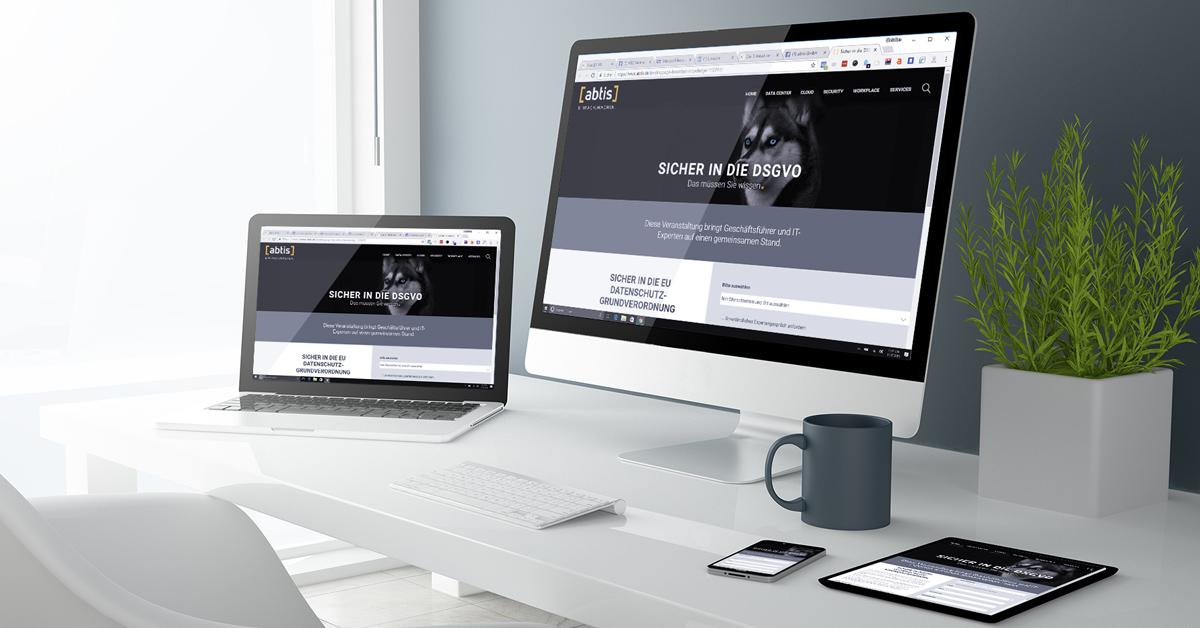 Auf einem Arbeitstisch befinden sich ein Laptop, ein Desktop-Bildschirm, ein Tablet udn ein Smartphone, auf deren Bildschirmen eine Webseite zu sehen ist.