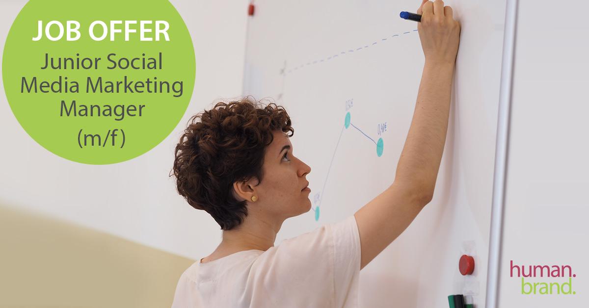 """Eine junge Frau schreibt auf einem Whiteboard. Links im Bild ist ein grünes Feld mit dem Text """"Job Offer Junior Social Media Marketing Manager (m/f)""""."""