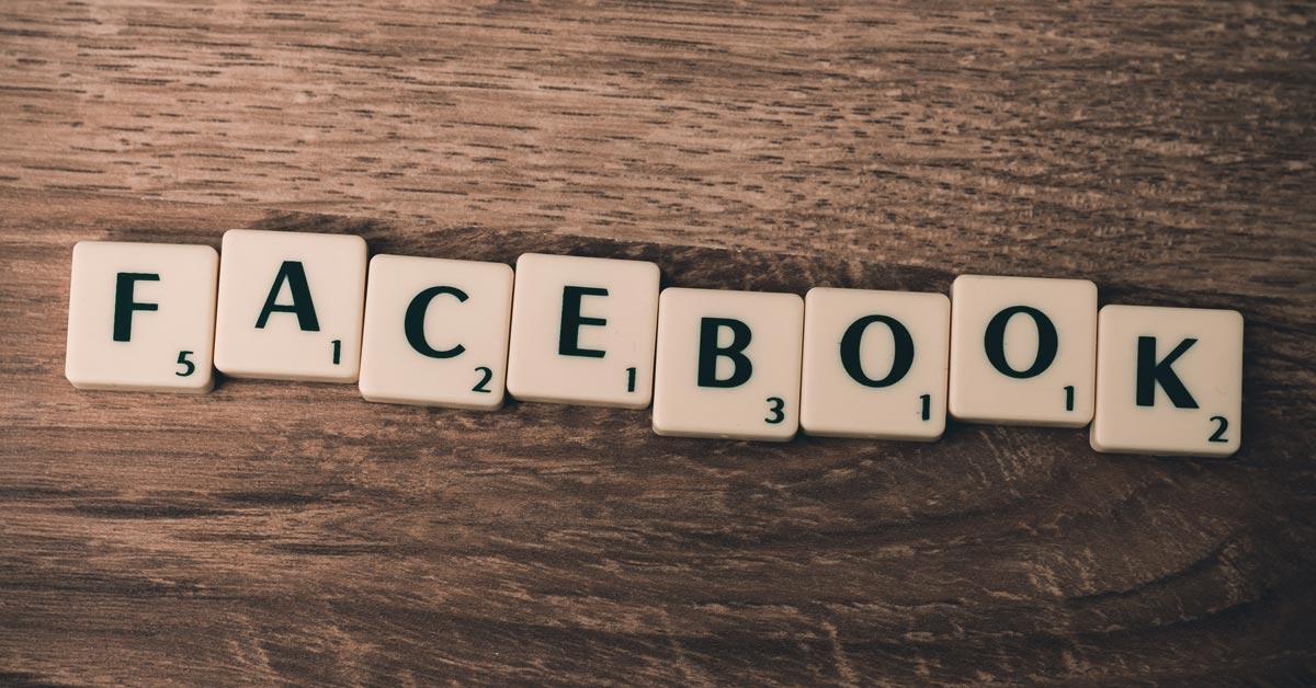 Auf einem hölzernen Untergrund liegen aneinander gereihte Scrabble-Spielsteine, die das Wort Facebook bilden.