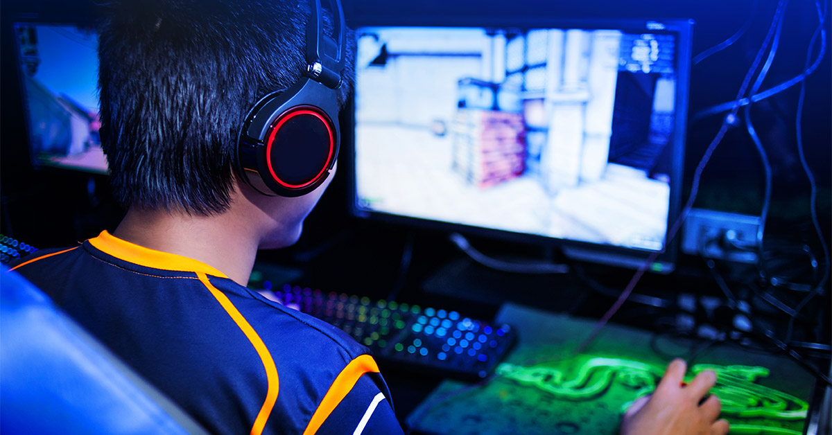 Das Bild zeigt einen Gamer beim Spielen eines Computerspiels.