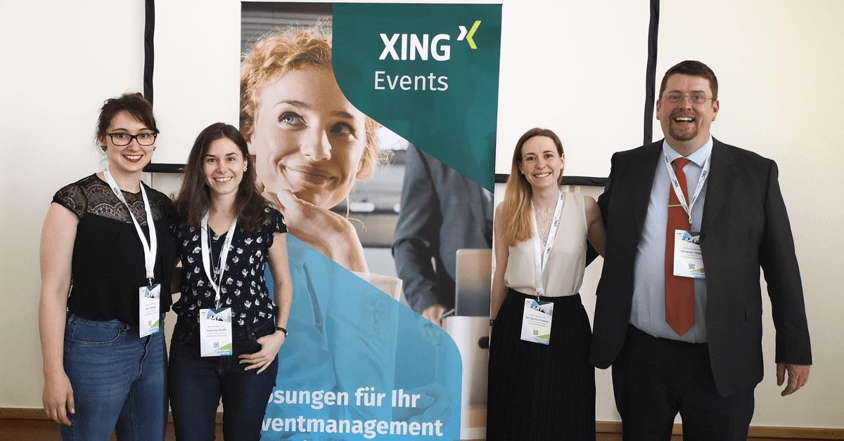 HUMANBRAND-Geschäftsführer Christian Haberl und drei seiner Mitarbeiterinnen stehen neben einem großen Werbebanner von XING Events.
