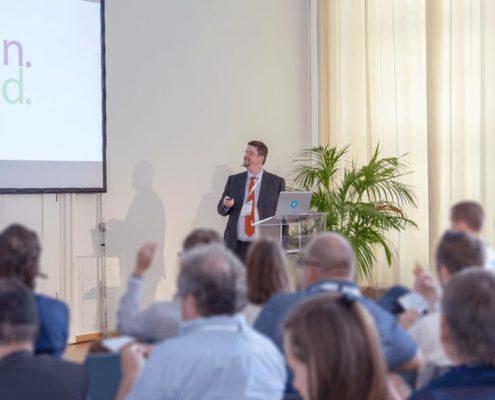 Das Bild zeigt HUMANBRAND-Geschäftsführer Christian Haberl während seines Vortrags vor interessiertem Publikum. Im Hintergrund ist das HUMANBRAND-Logo auf den Präsentationsfolien zu sehen.