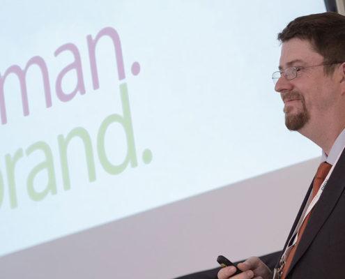 Das Bild zeigt HUMANBRAND-Geschäftsführer Christian Haberl während seines Vortrags. Im Hintergrund ist das HUMANBRAND-Logo auf den Präsentationsfolien zu sehen.