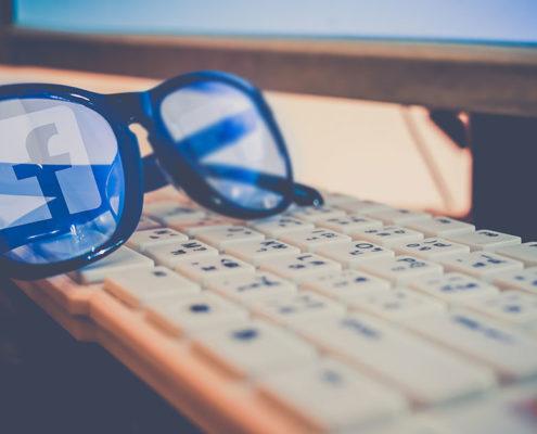 Auf einer Tastatur liegt eine Brille, in deren Gläsern sich das Facebook-Logo spiegelt.