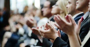 Man sieht applaudierende Menschen bei einem Event.