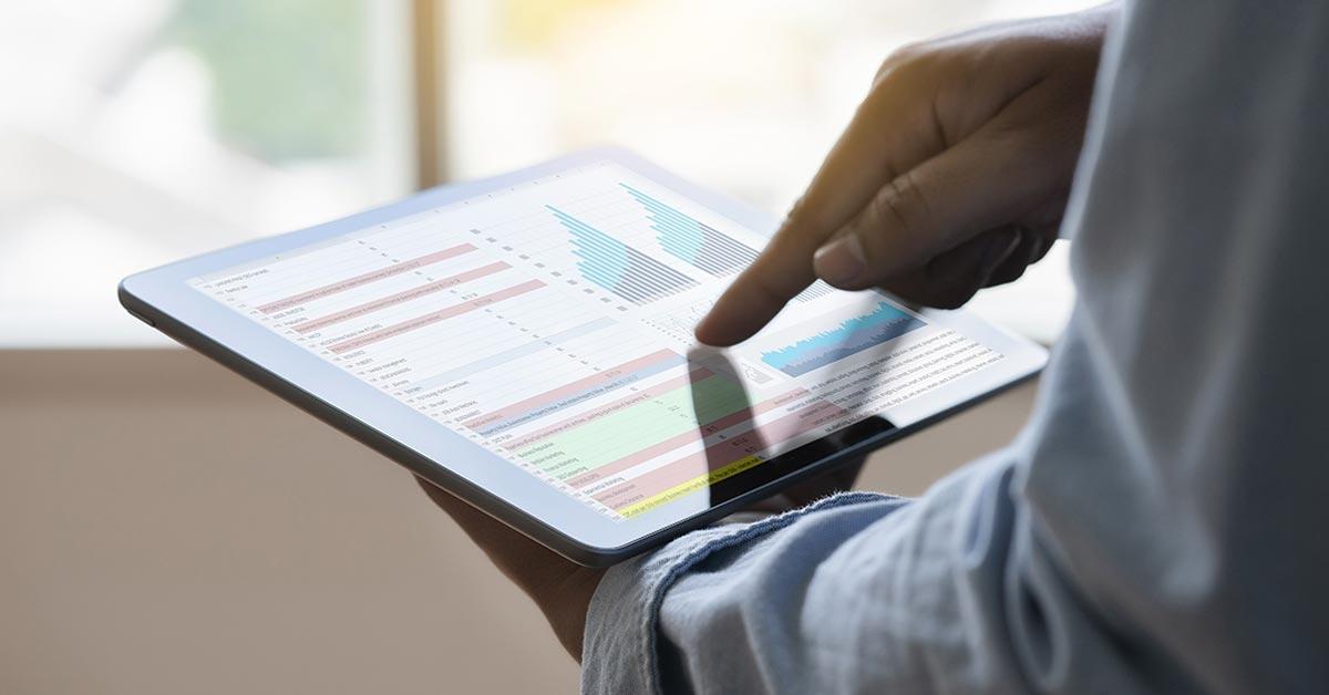 Eine Person hält ein Tablet in den Händen, auf dessen Bildschirm Auswertungen einer Werbekampagne zu sehen sind.