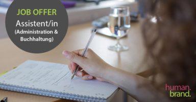 """Eine Frau macht auf einem Collegeblock Notizen. Links im Bild ist ein graues Feld mit dem Text """"Job Offer Assistent/in (Administration & Buchhaltung)""""."""