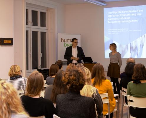 Ein Publikum lauscht zwei Vortragenden bei einer Präsentation über die intelligente Kombination aus effektiver Vermarktung und datengetriebenem Teilnehmermanagement.