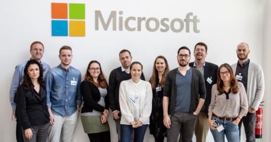 Teilnehmer des Paid Social Media Workshops posieren unterhalb eines großen Microsoft-Logos.