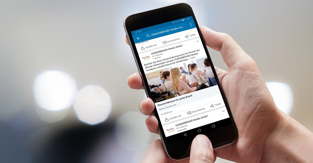 Auf dem Bildschirm eines Smartphones ist die LinkedIn-App und darin LinkedIn-Ads von HUMANBRAND zu sehen.