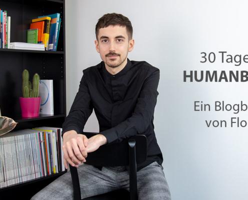 Florian sitzt auf einem Stuhl, im Hintergrund steht ein Bücherregal.