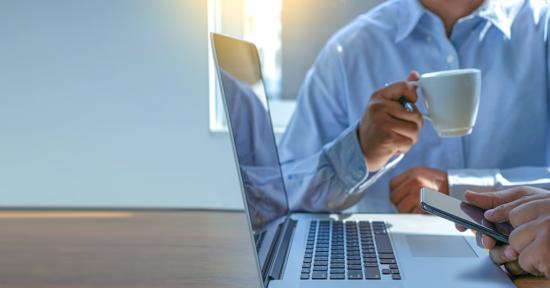 Auf dem Bild sieht man 2 Social Media Manager, die vor einem Laptop sitzen. Einer hält ein Smartphone in der Hand, der andere eine Tasse Kaffee.