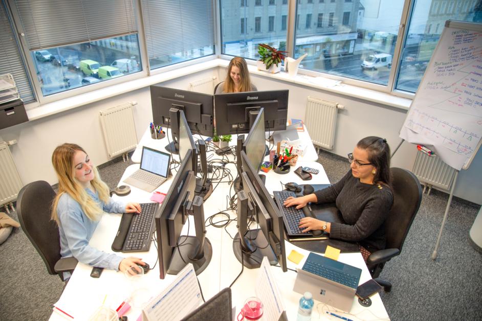 Auf dem Bild sieht man Kathi, Marie und Nazy bei der Arbeit vor Ihren Computerbildschirmen.
