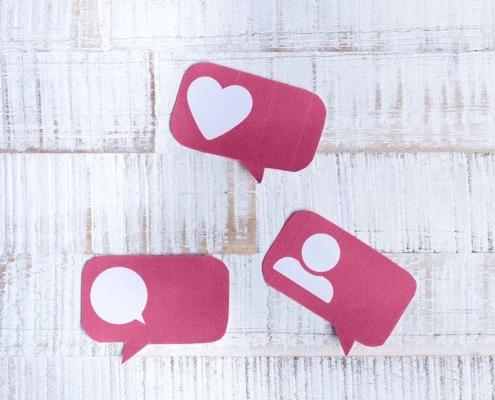 Auf dem Bild sieht man 3 rosa Sprechblasen auf einem weißen, hölzernen Untergrund, die für Like, Comment & Follower stehen.