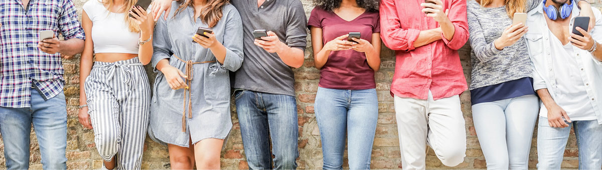 Auf dem Bild lehnt eine Gruppe an Influencern an einer Mauer stehen. Sie haben alle ihre Smartphones in der Hand.